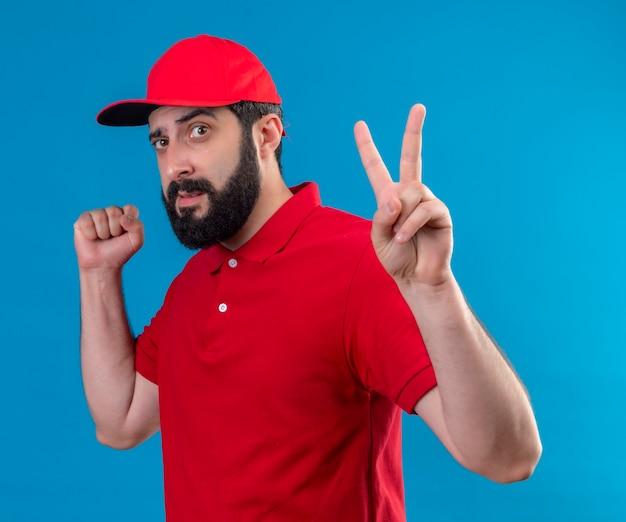 Zuversichtlich junger hübscher kaukasischer liefermann, der rote uniform und kappe trägt, die in der profilansicht stehen und friedenszeichen und geballte faust tun, die auf blau lokalisiert werden
