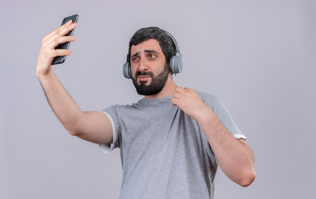 Zuversichtlich junger hübscher kaukasischer mann, der kopfhörer hält, die sein hemd halten und selfie lokalisiert auf weiß mit kopienraum nehmen
