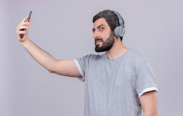 Zuversichtlich junger hübscher kaukasischer mann, der kopfhörer trägt und handy lokalisiert auf weiß hält