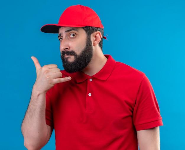 Zuversichtlich junger hübscher kaukasischer zusteller, der rote uniform und kappe tut, die anrufgeste lokalisiert auf blau trägt