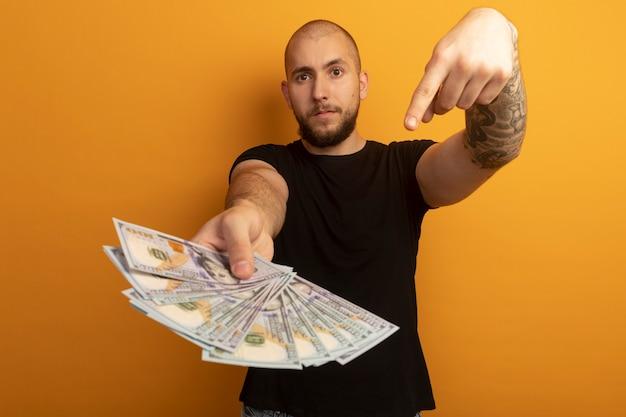 Zuversichtlich junger hübscher kerl, der schwarzes hemd hält und auf bargeld zeigt