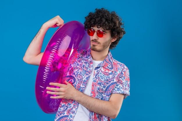 Zuversichtlich junger hübscher lockiger mann, der sonnenbrillen hält, die schwimmring halten starke geste auf lokalisiertem blauem raum mit kopienraum tun