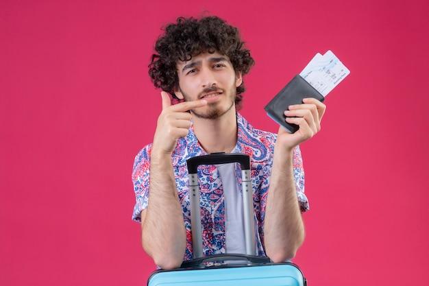 Zuversichtlich junger hübscher lockiger reisender mann, der brieftasche und flugtickets hält, die auf sie zeigen und arme auf koffer auf isoliertem rosa raum mit kopienraum setzen