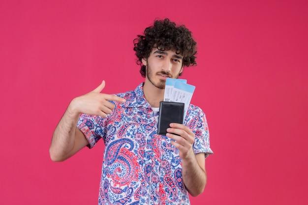 Zuversichtlich junger hübscher lockiger reisender mann, der flugtickets, geldbörse hält und auf sie auf lokalisiertem rosa raum mit kopienraum zeigt