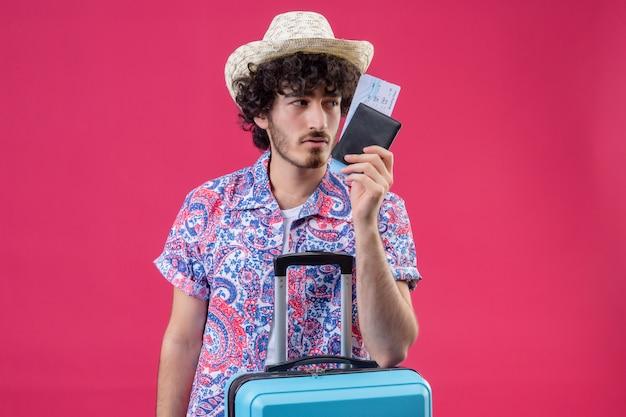 Zuversichtlich junger hübscher lockiger reisender mann, der hut hält, der brieftasche und flugtickets hält und arm auf koffer setzt, der auf der rechten seite auf isoliertem rosa raum mit kopienraum schaut
