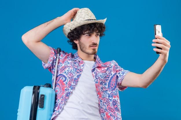 Zuversichtlich junger hübscher lockiger reisender mann, der hut nimmt, der selfie hand auf hut mit koffer auf isoliertem blauem raum setzt