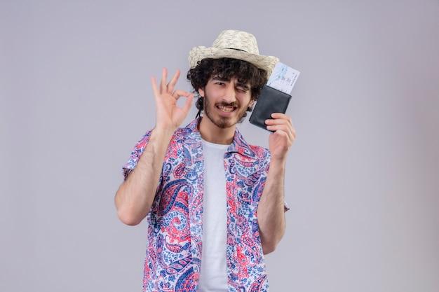 Zuversichtlich junger hübscher lockiger reisender mann, der hut tut, der ok zeichen tut, brieftasche und flugtickets auf isoliertem weißem raum mit kopienraum zeigt