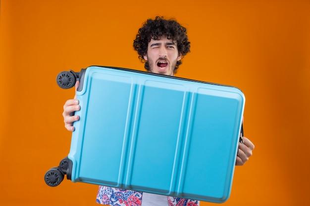 Zuversichtlich junger hübscher lockiger reisender mann, der koffer hält und mit offenem mund auf lokalisiertem orange raum zwinkert