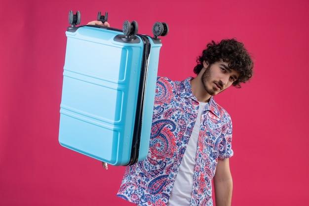 Zuversichtlich junger hübscher lockiger reisender mann, der koffer mit einer hand auf lokalisiertem rosa raum erhebt