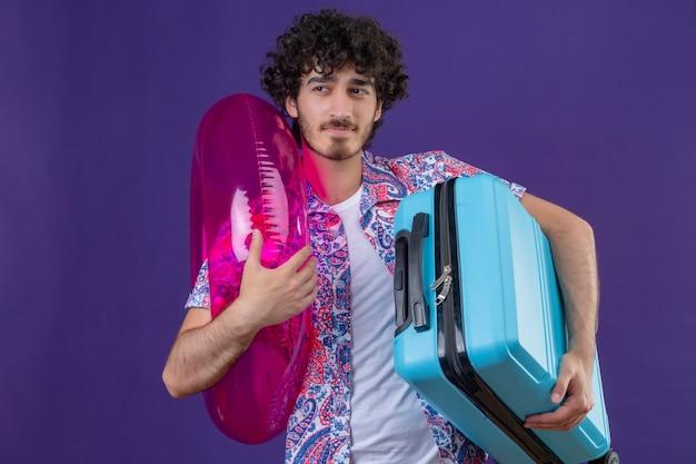 Zuversichtlich junger hübscher lockiger reisender mann, der koffer und schwimmring hält, die linke seite auf lokalisiertem lila raum mit kopienraum betrachten