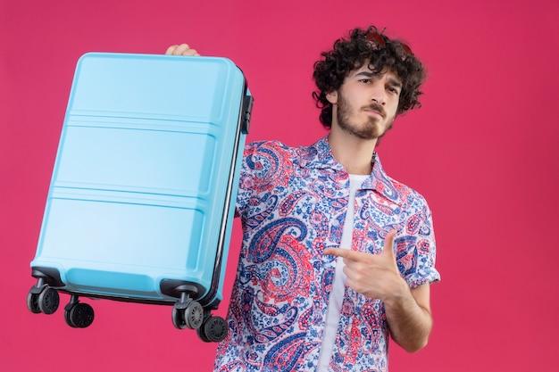 Zuversichtlich junger hübscher lockiger reisender mann, der sonnenbrille auf kopf hält, der koffer zeigt, der auf lokalisiertem rosa raum zeigt