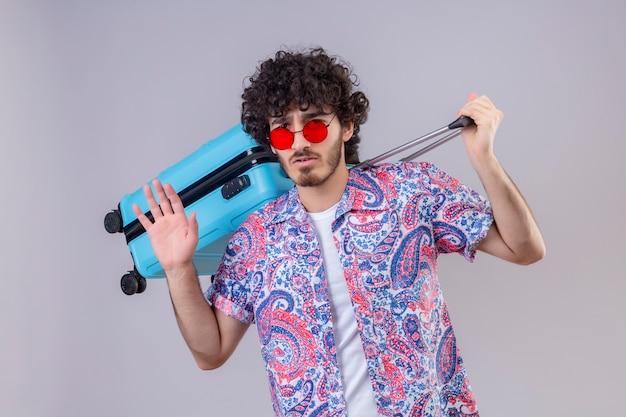 Zuversichtlich junger hübscher lockiger reisender mann, der sonnenbrille hält, koffer auf seinem rücken hält und tschüss auf isolierten weißen raum gestikuliert