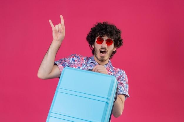 Zuversichtlich junger hübscher lockiger reisender mann, der sonnenbrille hält, koffer hält und rockzeichen auf lokalisiertem rosa raum mit kopienraum tut
