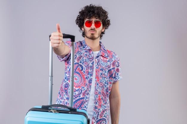Zuversichtlich junger hübscher lockiger reisender mann, der sonnenbrille mit koffer auf isoliertem weißem raum mit kopienraum trägt