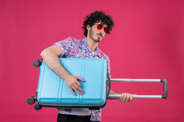 Zuversichtlich junger hübscher lockiger reisender mann, der sonnenbrille trägt und koffer als gitarre auf lokalisiertem rosa raum verwendet