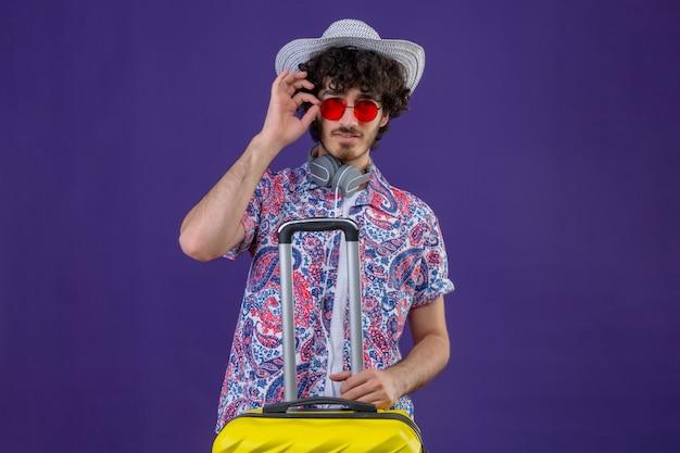 Zuversichtlich junger hübscher lockiger reisender mann, der sonnenbrille und hut hält, koffer hält und hand auf brille auf isoliertem lila raum mit kopienraum setzt