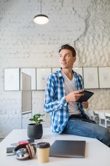 Zuversichtlich junger hübscher mann im chekered hemd, das auf tisch unter verwendung des tablet-computers im mitarbeitenden büro sitzt