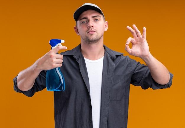 Zuversichtlich junger hübscher reinigungsmann, der t-shirt und kappe hält, die sprühflasche hält und okay geste zeigt, die auf orange wand lokalisiert wird