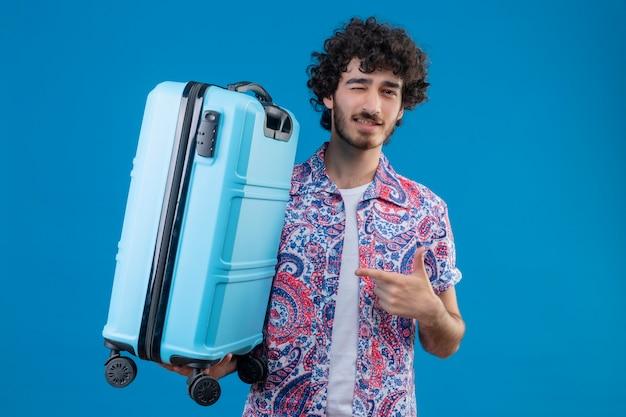 Zuversichtlich junger hübscher reisender mann, der koffer hält, der darauf zeigt und auf isoliertem blauem raum mit kopienraum zwinkert