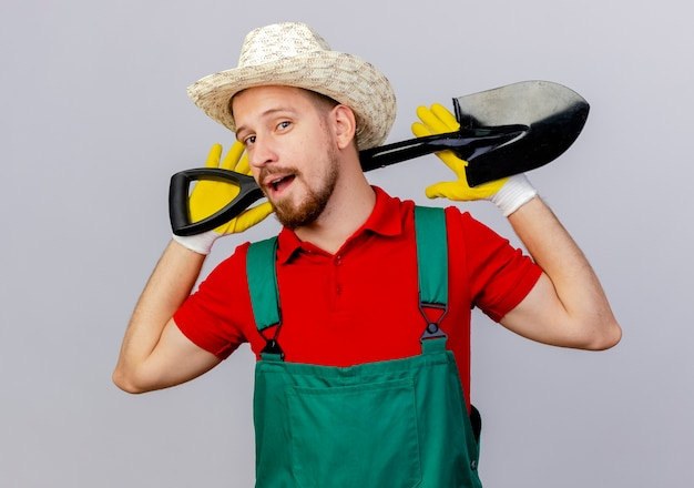 Zuversichtlich junger hübscher slawischer gärtner in der uniform, die gartenhandschuhe und hut hält, der spaten hinter hals lokalisiert auf weißer wand hält