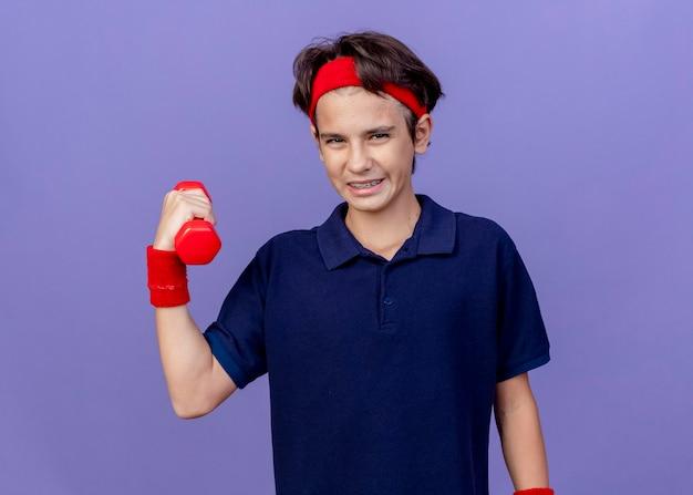 Zuversichtlich junger hübscher sportlicher junge, der stirnband und armbänder mit zahnspangen hält, die hantel lokalisiert auf lila wand mit kopienraum halten