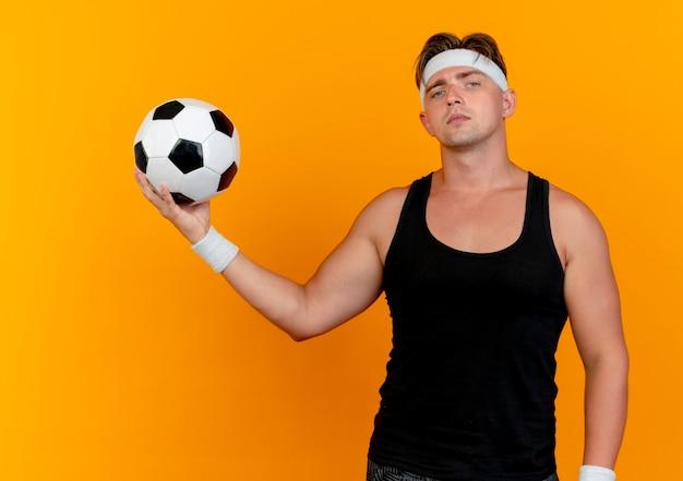 Zuversichtlich junger hübscher sportlicher mann, der stirnband und armbänder hält, die fußball suchen, der auf orange lokalisiert schaut