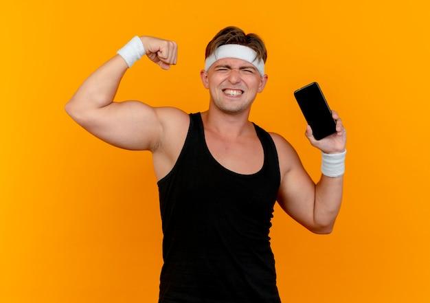 Zuversichtlich junger hübscher sportlicher mann, der stirnband und armbänder hält, die handy halten und stark lokalisiert auf orange gestikulieren