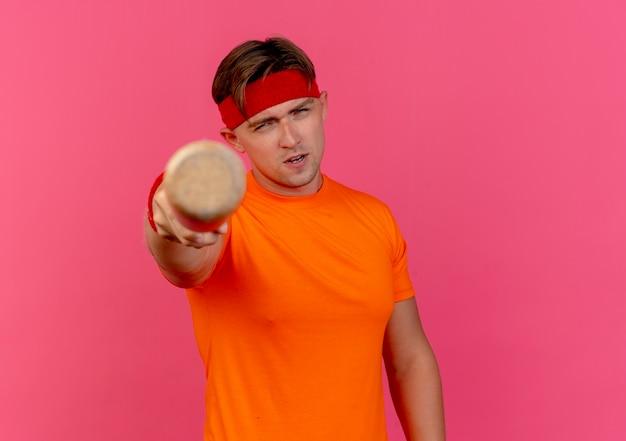 Zuversichtlich junger hübscher sportlicher mann, der stirnband und armbänder trägt, die baseballschläger in richtung kamera strecken, die auf rosa mit kopienraum lokalisiert wird