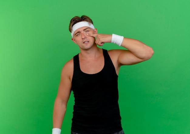 Zuversichtlich junger hübscher sportlicher mann, der stirnband und armbänder trägt, die finger unter auge lokalisiert auf grün mit kopienraum setzen