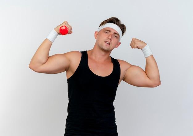 Zuversichtlich junger hübscher sportlicher mann, der stirnband und armbänder trägt, die stark mit hantel in der hand lokalisiert auf weiß gestikulieren