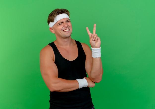 Zuversichtlich junger hübscher sportlicher mann, der stirnband und armbänder zwinkert, die friedenszeichen tun und hand unter ellbogen lokalisiert auf grün mit kopienraum setzen