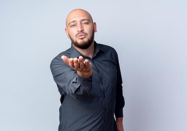 Zuversichtlich junger kahlköpfiger call-center-mann, der schlagkuss sendet und hand streckt, die auf weiß mit kopienraum lokalisiert wird