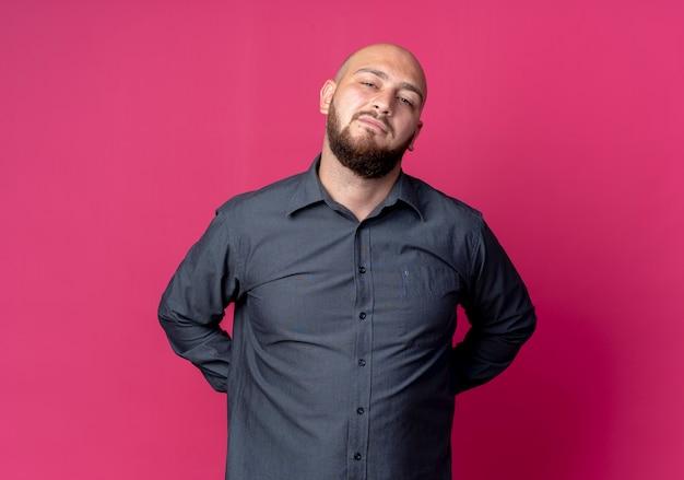 Zuversichtlich junger kahlköpfiger callcenter-mann, der hände hinter dem rücken hält und isoliert auf purpur mit kopienraum schaut