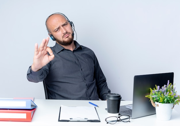 Zuversichtlich junger kahlköpfiger callcenter-mann, der headset am schreibtisch mit arbeitswerkzeugen sitzt, die ok zeichen lokalisiert auf weiß tun