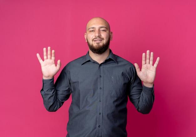 Zuversichtlich junger kahlköpfiger callcenter-mann, der leere hände zeigt, die auf purpur isoliert werden