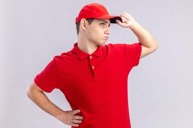Zuversichtlich junger kaukasischer lieferbote in rotem hemd, der seine mütze hält und die seite isoliert auf weißer wand mit kopienraum betrachtet