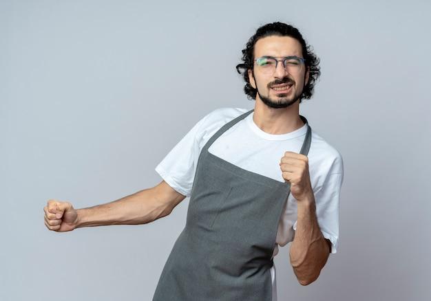Zuversichtlich junger kaukasischer männlicher friseur, der brille und gewelltes haarband im einheitlichen zwinkernden und geballten fäusten trägt, lokalisiert auf weißem hintergrund