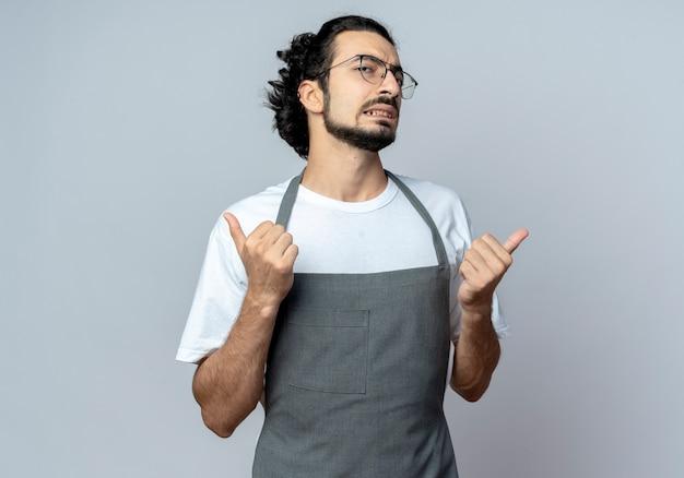 Zuversichtlich junger kaukasischer männlicher friseur, der brille und gewelltes haarband in der uniform zeigt, die daumen oben lokalisiert auf weißem hintergrund mit kopienraum zeigt