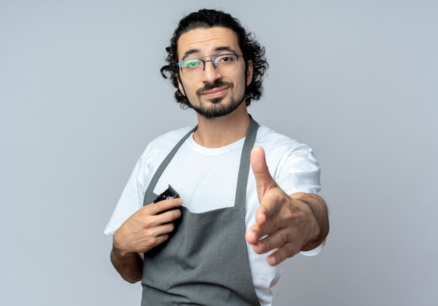 Zuversichtlich junger kaukasischer männlicher friseur, der brille und welliges haarband in uniform hält, die haarschneidemaschinen ausstreckt, die hand an der kamera ausstrecken, die hallo lokalisiert auf weißem hintergrund mit kopienraum gestikuliert