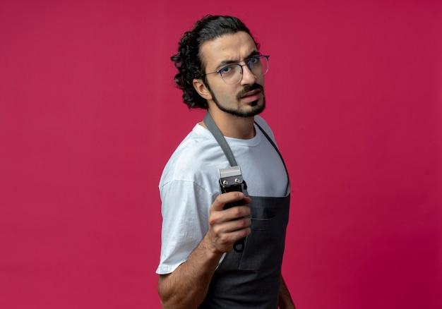 Zuversichtlich junger kaukasischer männlicher friseur, der brille und welliges haarband in uniform hält haarschneidemaschinen lokalisiert auf purpurrotem hintergrund mit kopienraum