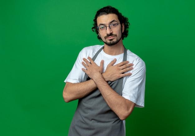 Zuversichtlich junger kaukasischer männlicher friseur, der brille und welliges haarband in uniform trägt, die hände gekreuzt auf brust lokalisiert auf grünem hintergrund mit kopienraum