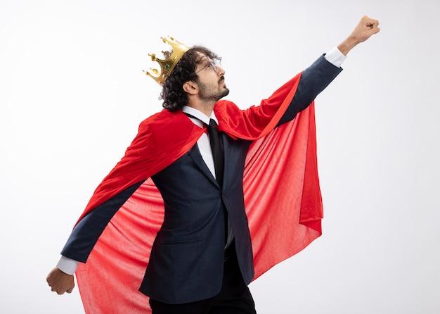 Zuversichtlich junger kaukasischer superheldenmann in der optischen brille, die anzug mit rotem umhang und krone steht, hält seitlich die arme offen und hebt die faust hoch, isoliert auf weißer wand