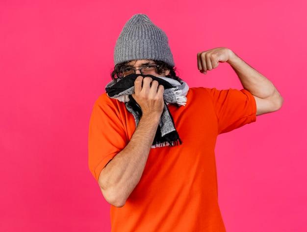 Zuversichtlich junger kranker mann, der brille wintermütze und schal bedeckt mund mit schal, der nach vorne schaut starke geste auf rosa wand lokalisiert