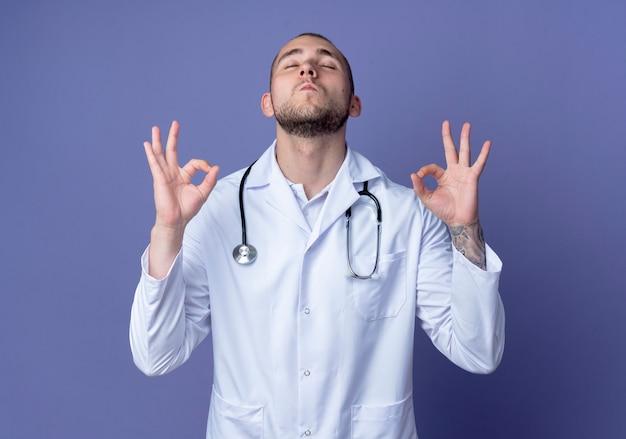 Zuversichtlich junger männlicher arzt, der medizinische robe und stethoskop trägt, die ok zeichen mit geschlossenen augen tun, die auf purpur mit kopienraum isoliert werden