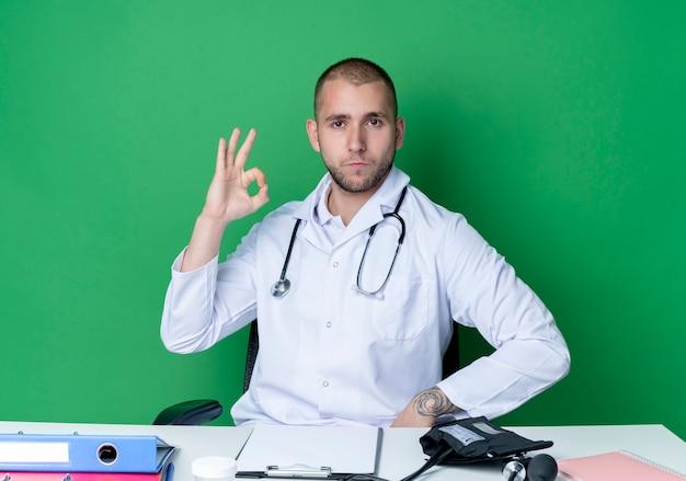 Zuversichtlich junger männlicher arzt, der medizinische robe und stethoskop trägt, sitzt am schreibtisch mit arbeitswerkzeugen, die ok zeichen lokalisiert auf grün tun