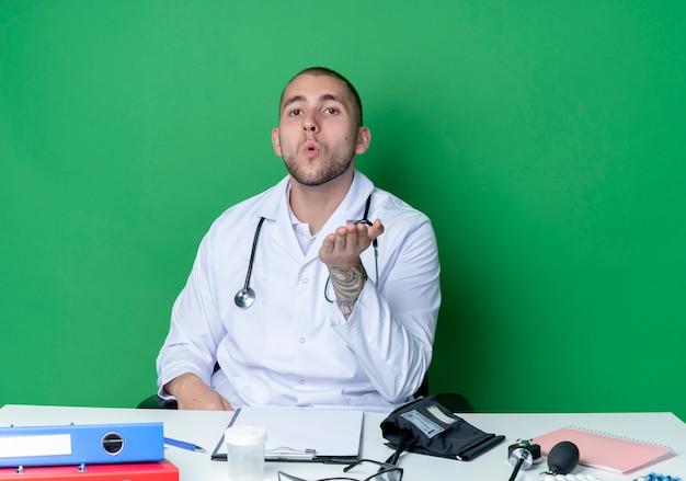 Zuversichtlich junger männlicher arzt, der medizinisches gewand und stethoskop trägt, sitzt am schreibtisch mit arbeitswerkzeugen, die schlagkuss senden und mit hand in der luft lokalisiert auf grün suchen