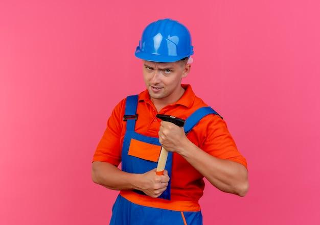 Zuversichtlich junger männlicher baumeister, der uniform und schutzhelm hält hammer hält