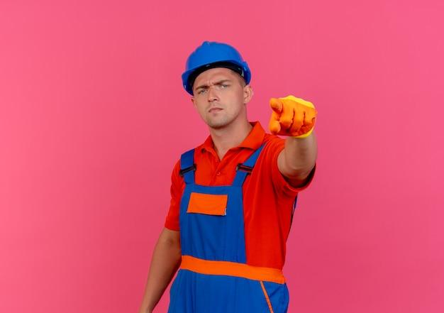 Zuversichtlich junger männlicher baumeister, der uniform und schutzhelm in handschuhen trägt, die sie geste zeigen