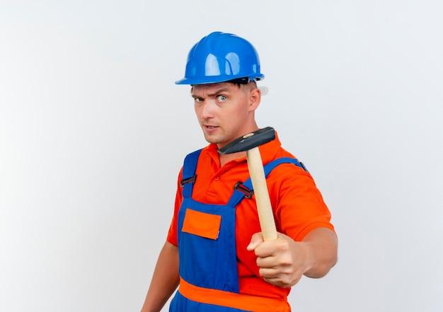 Zuversichtlich junger männlicher baumeister, der uniform und schutzhelm trägt, der hammer heraushält