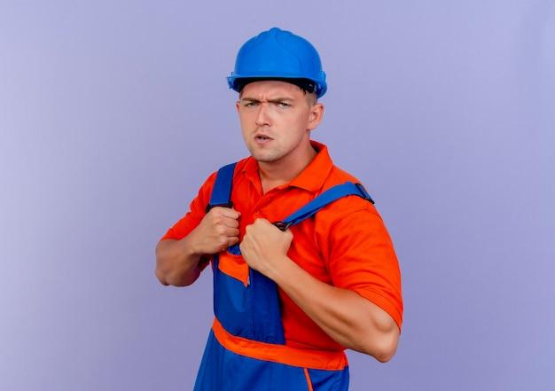 Zuversichtlich junger männlicher baumeister, der uniform und schutzhelm trägt, griff nach uniform